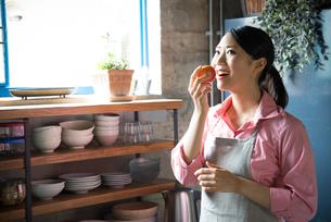 キッチンでりんごを食べようとしている女性の素材 [FYI01078736]