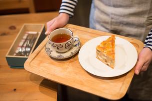 ケーキと紅茶が載っているトレイを持っている女性の手の素材 [FYI01078754]