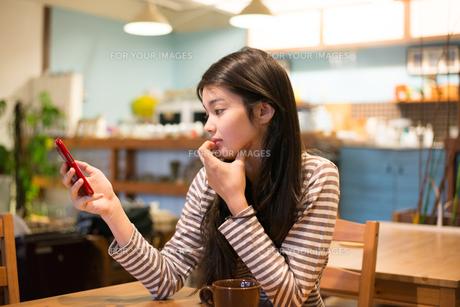 カフェで携帯を見ている女性の素材 [FYI01078757]