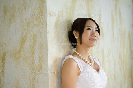 壁にもたれるドレス姿の女性の素材 [FYI01078765]