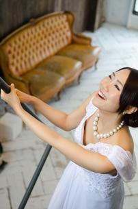 手すりを触りながら笑うドレス姿の女性の素材 [FYI01078767]