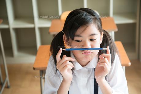鼻の下に鉛筆を挟んでいる小学生の女の子の素材 [FYI01078771]