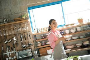 キチンでお皿を持っている女性の素材 [FYI01078772]