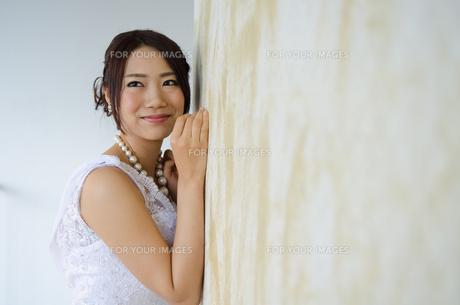 壁にもたれるドレス姿の女性の素材 [FYI01078793]