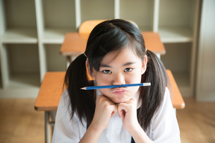 鼻の下に鉛筆を挟んでいる小学生の女の子の素材 [FYI01078800]