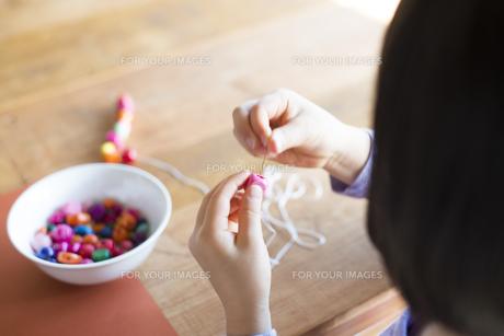 ビーズで遊んでいる女の子の手の素材 [FYI01078802]