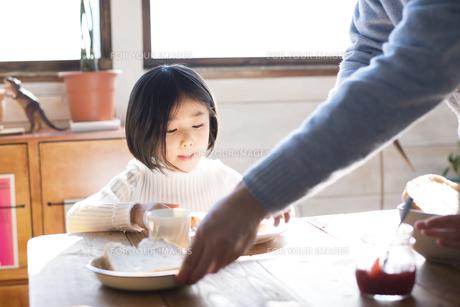 食卓にいる女の子とお父さんの手の素材 [FYI01078810]