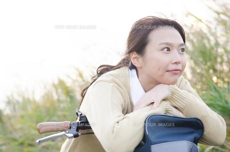 自転車のハンドルにもたれる女子学生の素材 [FYI01078824]
