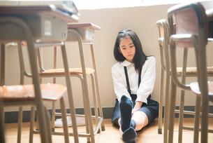 教室の床に座っている小学生の女の子の素材 [FYI01078826]