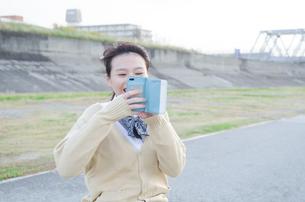 スマホで写真を撮っている女子学生の素材 [FYI01078835]