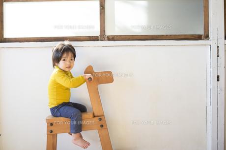 木馬に乗って遊ぶ男の子の素材 [FYI01078838]