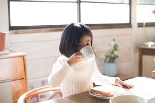 食卓でカップで飲み物を飲んでいる女の子の素材 [FYI01078852]