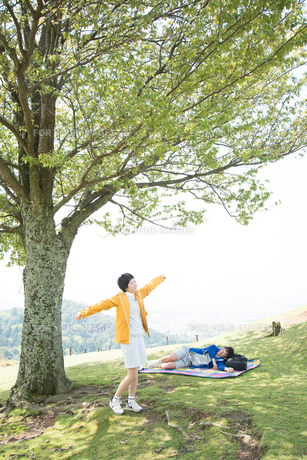 木の下で深呼吸をする女性と寝転がる男性の素材 [FYI01078861]