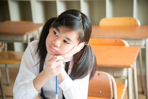 頬杖をついている小学生の女の子の素材 [FYI01078891]