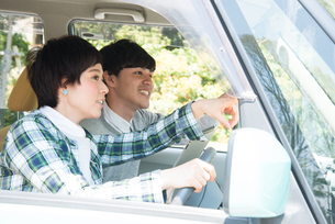車の中で方向を確かめている男女の素材 [FYI01078905]