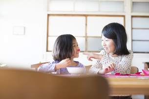 テーブルで遊んでいる姉妹の素材 [FYI01078966]