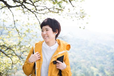 木をバックに笑っている女性の素材 [FYI01078999]