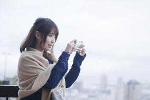 展望台から神戸の景色の写真を撮る女性の素材 [FYI01096512]