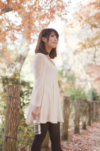 秋の紅葉した公園で立ってペットボトルを持っている女性の素材 [FYI01096524]