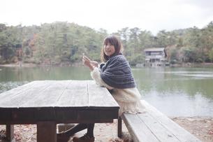 公園のテーブルで携帯をさわるニットセーターを着た女性の素材 [FYI01096525]