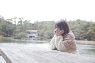 公園のテーブルに肘を付くニットセーターを着た女性の素材 [FYI01096529]