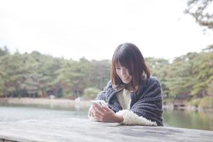 公園のテーブルで携帯をさわるニットセーターを着た女性の素材 [FYI01096531]