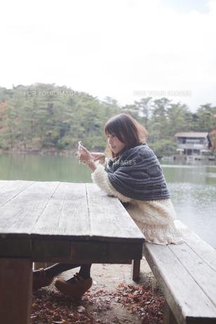 公園のテーブルで携帯をさわるニットセーターを着た女性の素材 [FYI01096533]