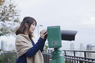 展望台から双眼鏡で神戸の景色を望む笑顔の女性の素材 [FYI01096541]