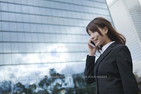 ビルの前で電話をするビジネスウーマンの素材 [FYI01096544]