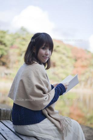 秋の紅葉の公園の池の前のベンチで本を読む女性の素材 [FYI01096547]