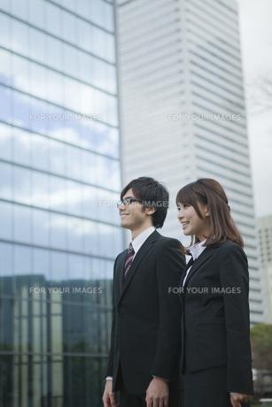 ビルの前で立つビジネスウーマンとビジネスマンの素材 [FYI01096554]