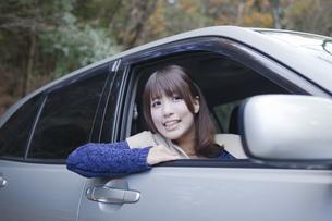 秋の紅葉の公園の駐車場で車の運転をする女性の素材 [FYI01096556]