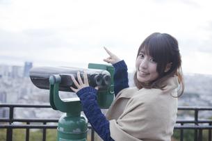 展望台から双眼鏡で神戸の景色を望む笑顔の女性の素材 [FYI01096557]