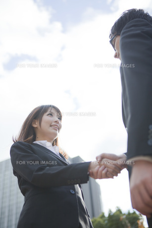 ビルの前で握手をするビジネスウーマンとビジネスマンの素材 [FYI01096558]