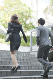 階段を駆け上がるビジネスマンとビジネスウーマンの素材 [FYI01096563]