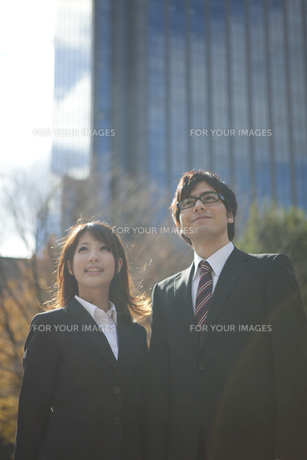ビルの前で立つビジネスウーマンとビジネスマンの素材 [FYI01096573]