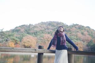 秋の紅葉の公園の池のほとりで伸びをする女性の素材 [FYI01096575]