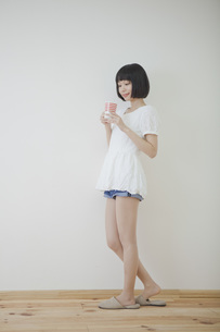 コップを持って立っている女性の素材 [FYI01096578]