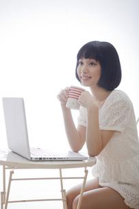 テーブルでコップを持ちながらパソコンを広げる女性の素材 [FYI01096592]