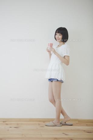 コップを持って立っている女性の素材 [FYI01096597]