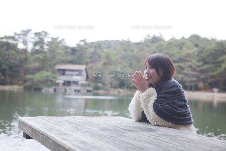 公園のテーブルに肘を付くニットセーターを着た女性の素材 [FYI01096602]