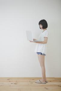 立ってパソコンを持つ女性の素材 [FYI01096607]
