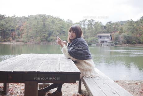 公園のテーブルで携帯をさわるニットセーターを着た女性の素材 [FYI01096612]