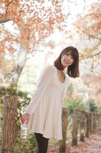秋の紅葉した公園で立ってペットボトルを持っている女性の素材 [FYI01096615]