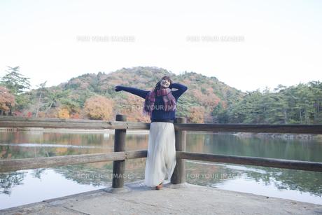 秋の紅葉の公園の池のほとりで伸びをする女性の素材 [FYI01096619]