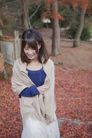 秋の紅葉の落ち葉の上の階段を歩く笑顔の女性の素材 [FYI01096620]