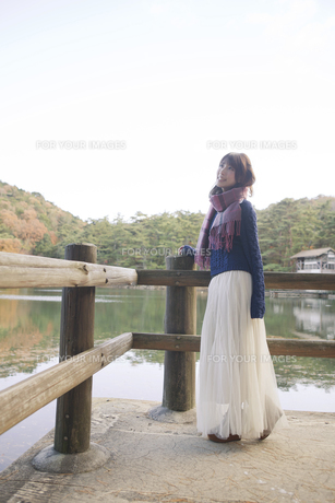 秋の紅葉の公園の池のほとりで池を見つめる女性の素材 [FYI01096622]