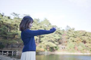 秋の紅葉の公園の池の前で写真を撮る笑顔の女性の素材 [FYI01096638]