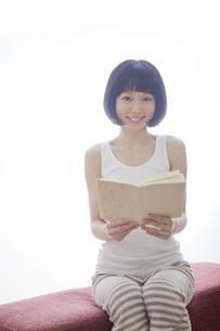 ソファで本を持つ笑顔の女性の素材 [FYI01096643]
