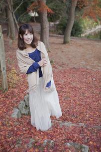 秋の紅葉の落ち葉の上の階段を歩く笑顔の女性の素材 [FYI01096652]